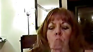 Attractive mature with slim body smokes a cigar while